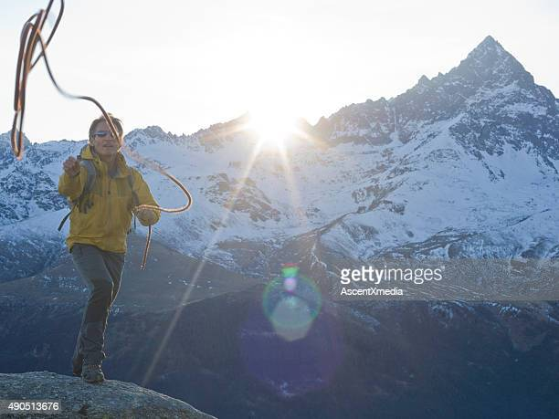 Climber throws out rope for teammate, above mountains