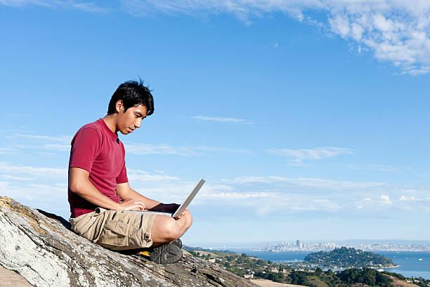 Climber using laptop on rocky hilltop