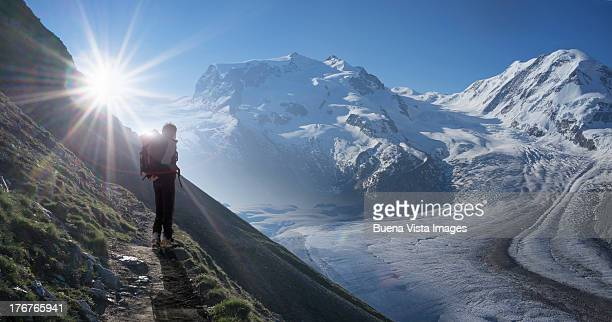 Climber watching a glacier at sunrise