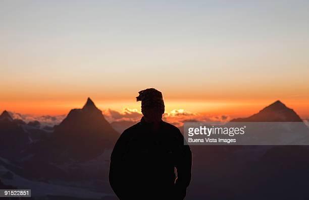 Climber watching sunset over Matterhorn