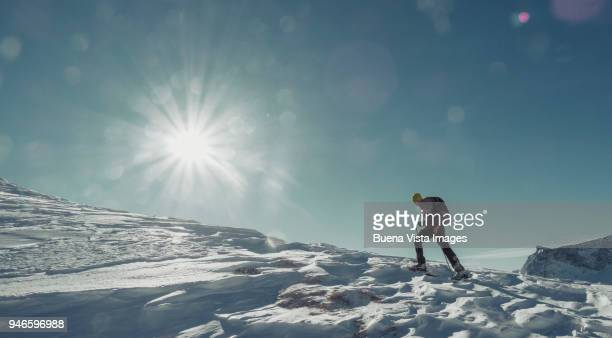 Climber with snow shoes on a snowy slope.