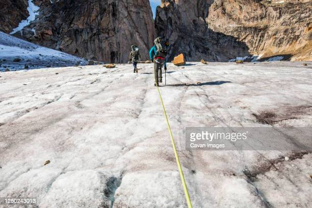 climbers approaching mountain summit, baffin island. - baffin island stock pictures, royalty-free photos & images