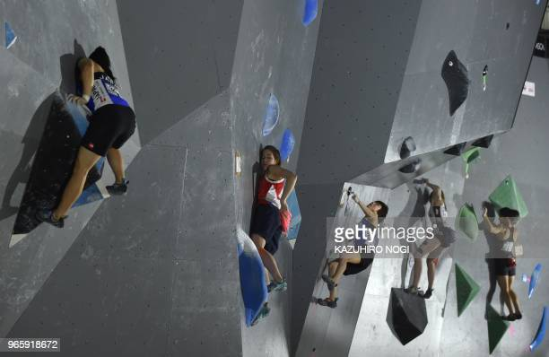 TOPSHOT Climbers compete during the women's bouldering qualification at the IFSC Climbing Worldcup competition in Hachioji Tokyo prefecture on June 2...
