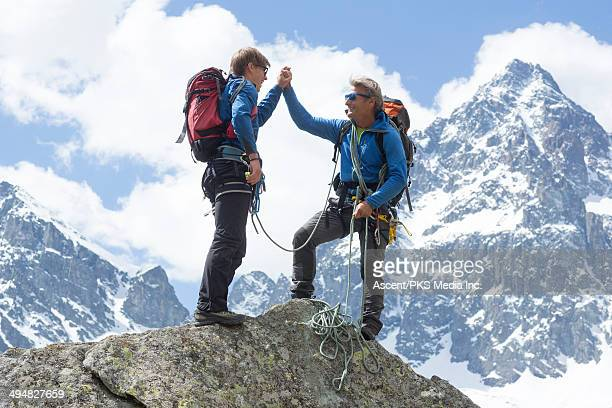 Climbers exchange high-fives on mountain summit