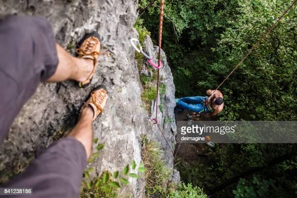 bergsteiger-übungen zu eine klippe klettern - subjektive kamera ungewöhnliche ansicht stock-fotos und bilder