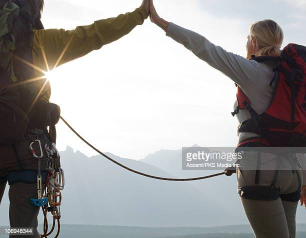 Climbers face distant mountains,exchange high-five