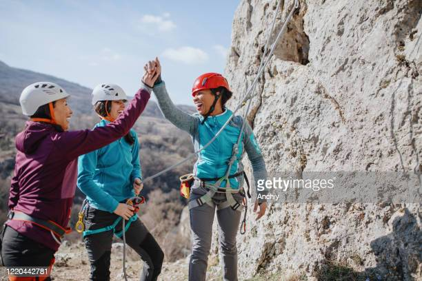 climbers giving high fives after successfully finishing climb - images stock pictures, royalty-free photos & images