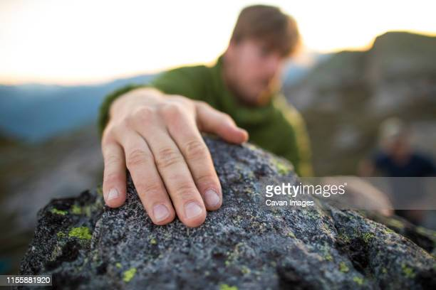 climbers hand grips a rock at the top of a bouldering route. - スクランブリング ストックフォトと画像