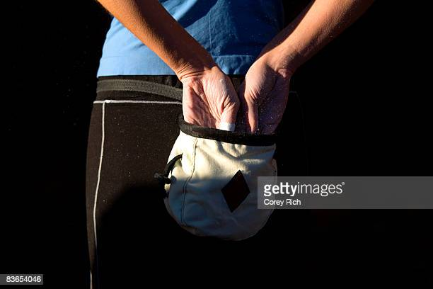 climber's hands reach into chalk bag - chalk bag stock pictures, royalty-free photos & images