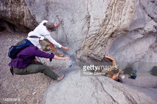 Climbers Helping Each Other Overcome Obstacle High Res