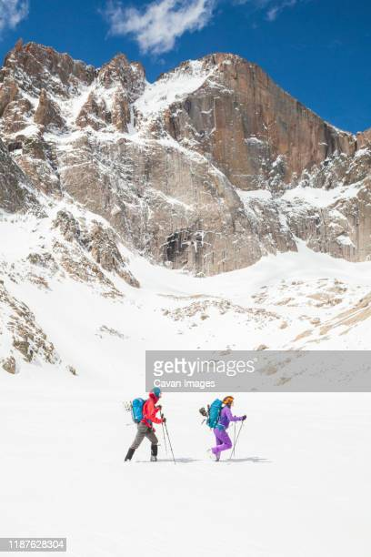 climbers hike below longs peak, rocky mountain national park - front range mountain range stock pictures, royalty-free photos & images