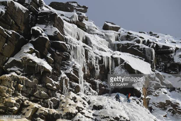 Climbers look for a route from Kinder Downfall waterfalls near the Kinder Scout plateau in the Peak District National Park near Hayfield, northwest...