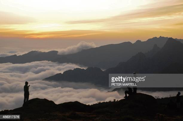 Climbers look out at sunset during a trek up Mount Kilimanjaro Tanzania on September 26 2014 Mount Kilimanjaro is a dormant volcanic mountain in...