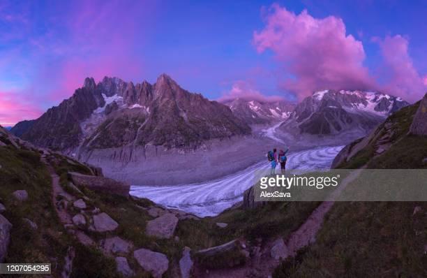 alpinistas olhando para o majestoso pôr do sol da montanha - cor saturada - fotografias e filmes do acervo
