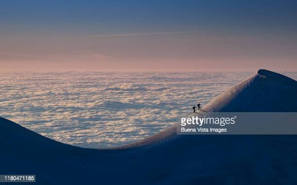climbers on a snowy ridge - condition stock pictures, royalty-free photos & images
