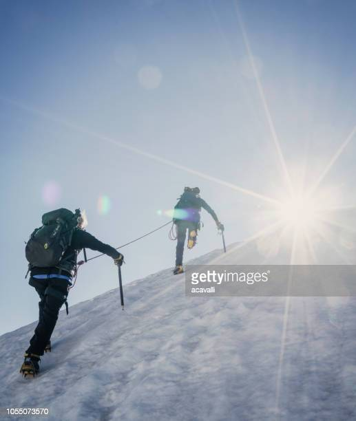 climbers on a snowy slope. - mountain climbing stock pictures, royalty-free photos & images