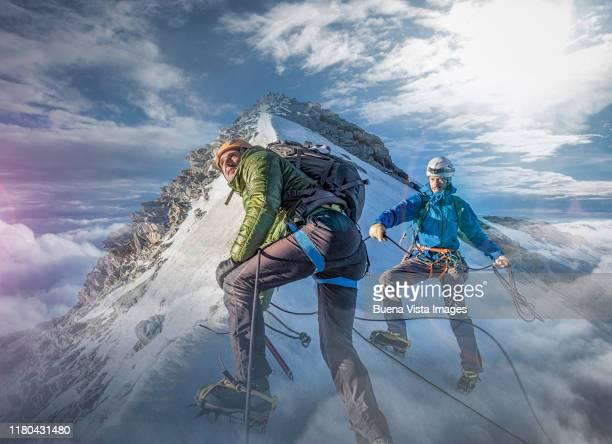 climbers on a snowy slope - climbing stock pictures, royalty-free photos & images