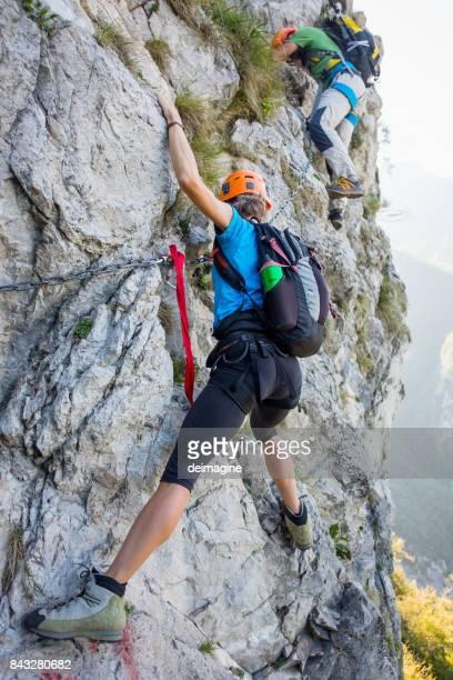 bergsteiger auf ausgestattete felswand - klettern stock-fotos und bilder