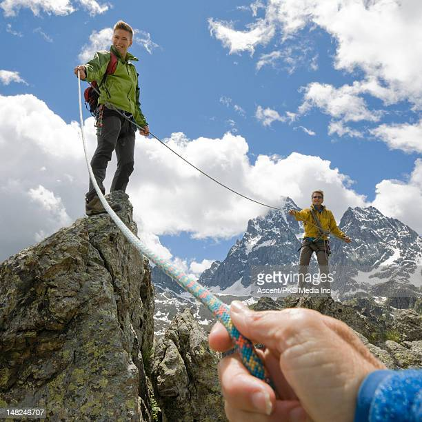 Climbers on ridge pull rope tight to teammate