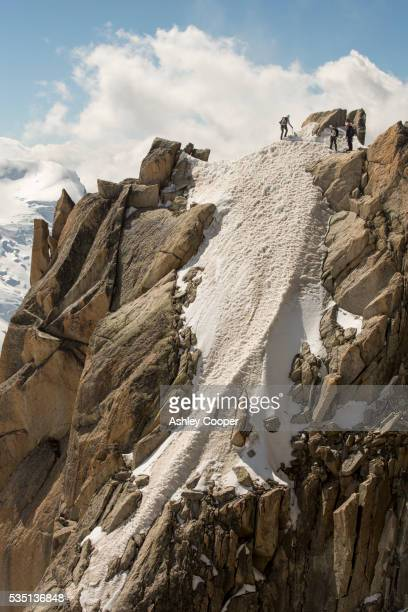 climbers on the cosmiques arete on the aiguille du midi above chamonix, france. - permafrost stock pictures, royalty-free photos & images
