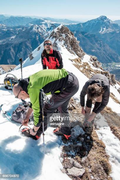 Climbers on the mountain top fasten crampon