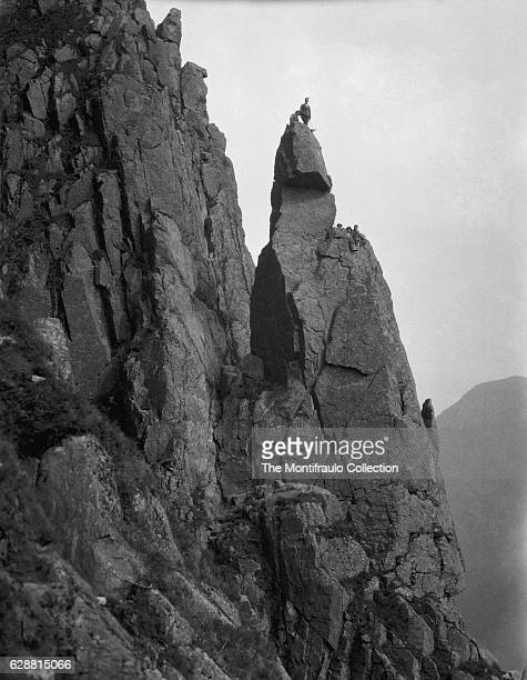 Climbers on the peak of Napes Needle, a prominent mountain rock pinnacle some 20 metres high situated on the southern flank of Great Gable, first...