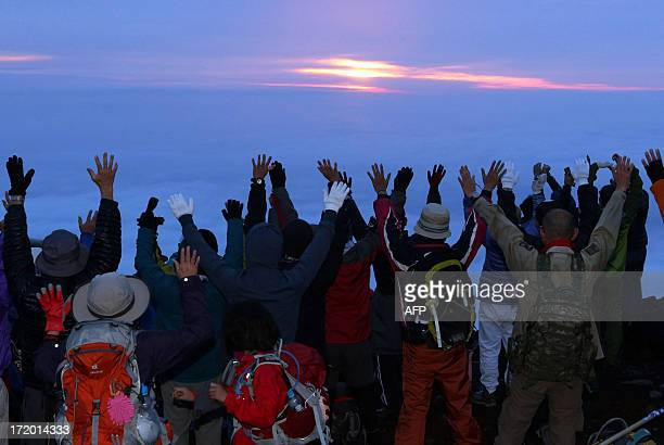 Climbers raise their hands in the air to celebrate the sunrise on the summit of Mount Fuji Japan's highest peak at 3776 meters as the 2013 climbing...