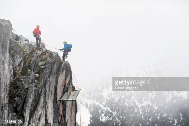 climbers rappelling onto portaledge on a vertical cliff face. - helmet stock pictures, royalty-free photos & images
