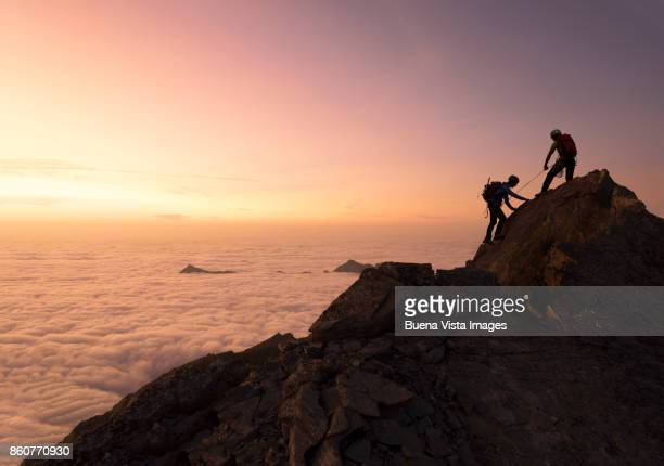 climbers reaching a mountain top. - summit stock pictures, royalty-free photos & images