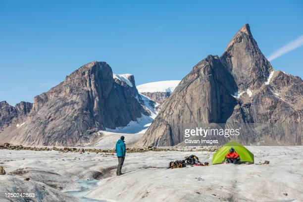 climbers relaxing at basecamp on glacier below mt. loki, baffin island - retreating ストックフォトと画像