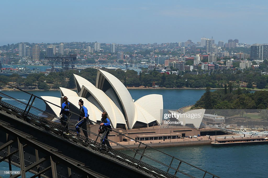 Climbers scale the Sydney Harbour Bridge during a guided tour operated by BridgeClimb as the Sydney Opera House stands in the background in Sydney, Australia, on Monday, Dec. 24, 2012. Beginning next month, people wanting to ascend 134 meters above sea level to the top of the bridge spanning Sydney Harbour will have the option to hear guides speak Mandarin. Photographer: Brendon Thorne/Bloomberg via Getty Images