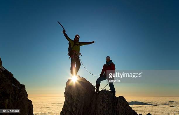 Kletterer stehen auf Felsen und Feiern