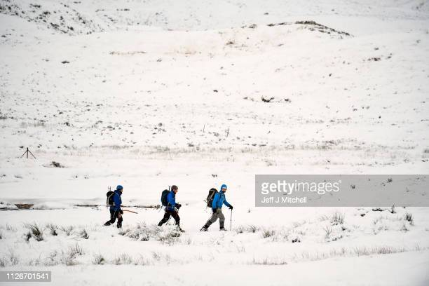 Climbers walk near Lagangarbh cottage below Buachaille Etive Mor on February 1, 2019 in Glen Coe Scotland. The Met office have yellow be aware...