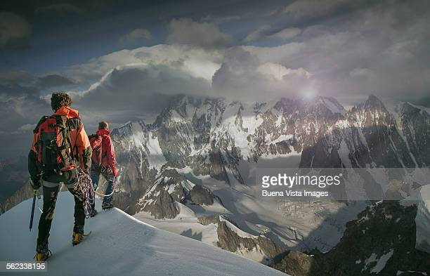 climbers watching a mountain in the clouds - monte bianco foto e immagini stock