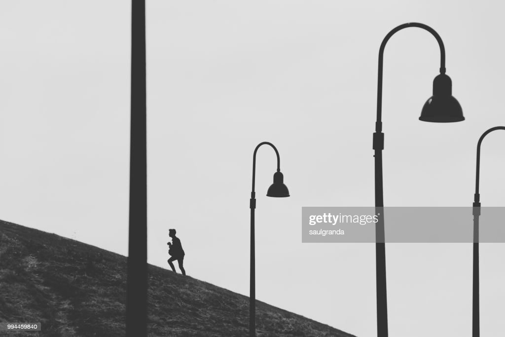 Climbing a hill with street lights in the foreground : Stock Photo