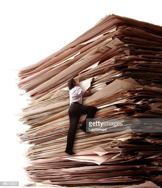climbing a pile of files - exceed and excel stock pictures, royalty-free photos & images