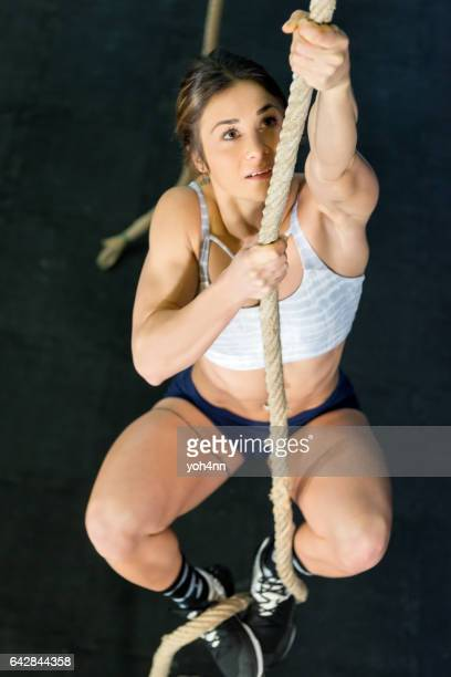 Climbing a rope at gym