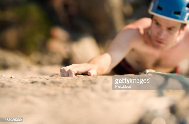 climbing a steep mountain face - nicky pende foto e immagini stock