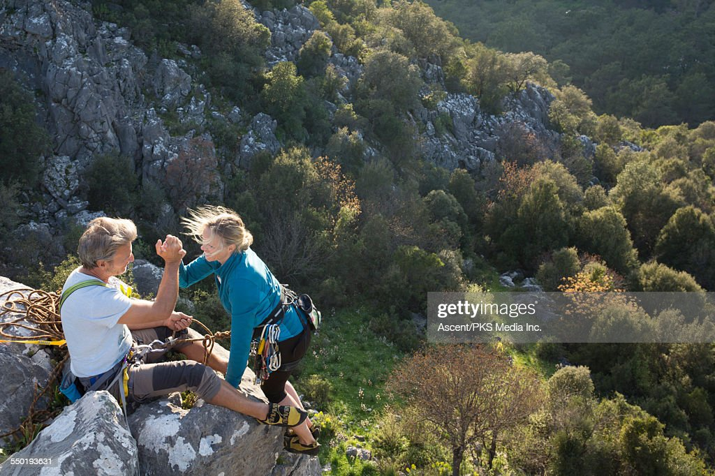Climbing couple exchange handshake, top of climb : Stock Photo