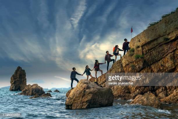 climbing group friends standing to hike up mountain .teamwork , helps ,success, winner and leadership concept . - teamevenement stockfoto's en -beelden