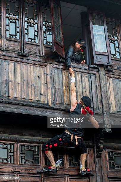 WUZHEN TONGXIANG ZHEJIANG CHINA Climbing on Chinese ancient architectures a French artist is performing his acrobatic show named 'Amour' The second...