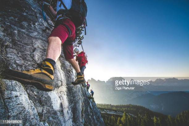 climbing on the mountaing edge - climbing stock pictures, royalty-free photos & images