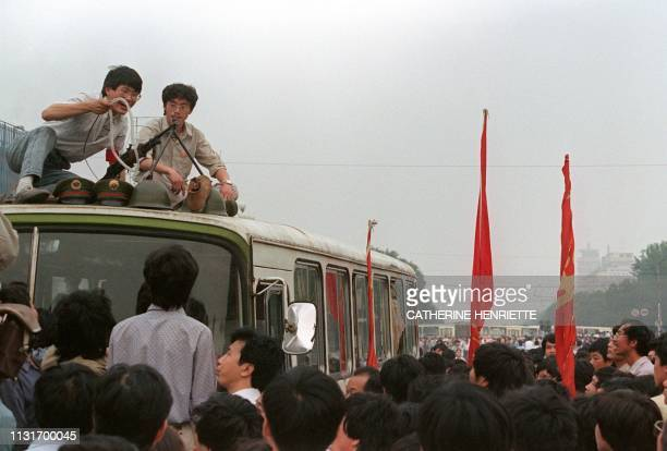 Climbing on the roof of a bus students displays confiscated machine gun helmet and military caps after they forced tens of thousands of troops to...