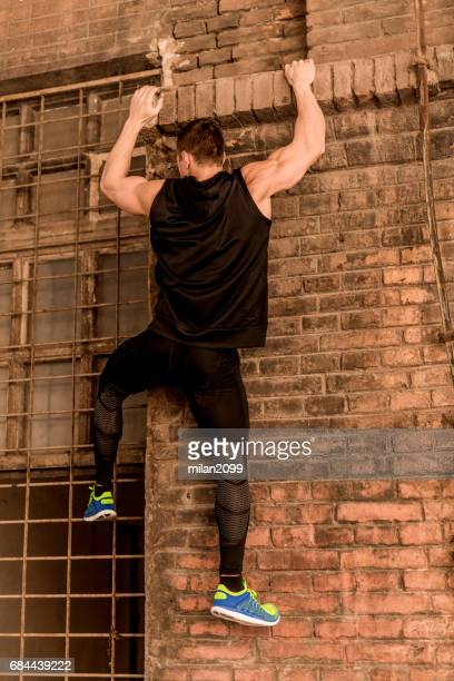 climbing on the wall - only young men stock pictures, royalty-free photos & images