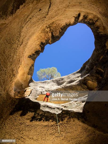 climbing speleologist, descending for the interior of a cave - un solo hombre stock photos and pictures