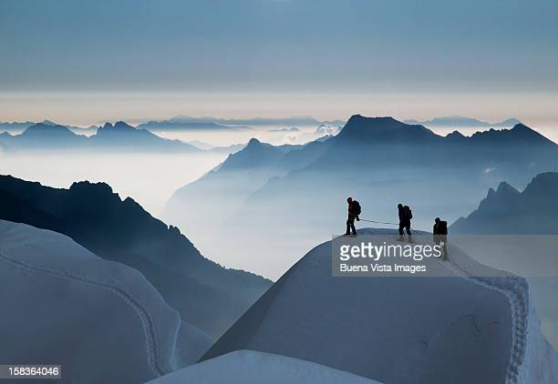 climbing team on a snowy ridge - buitensport stockfoto's en -beelden