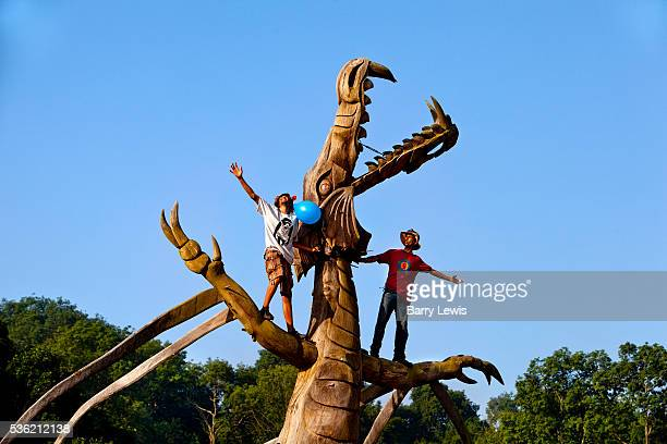 Climbing the wooden dragon to welcome the sunrise in the morning overlooking in the stone circle Glastonbury Festival 2010