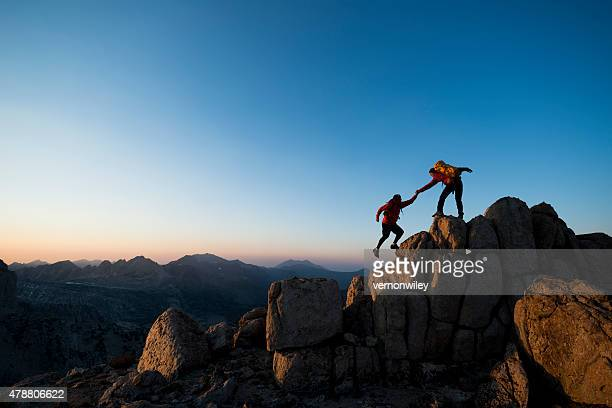 climbing to the top - hulp stockfoto's en -beelden