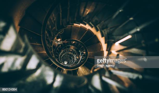climbing up the spiral stairs - staircase stock photos and pictures