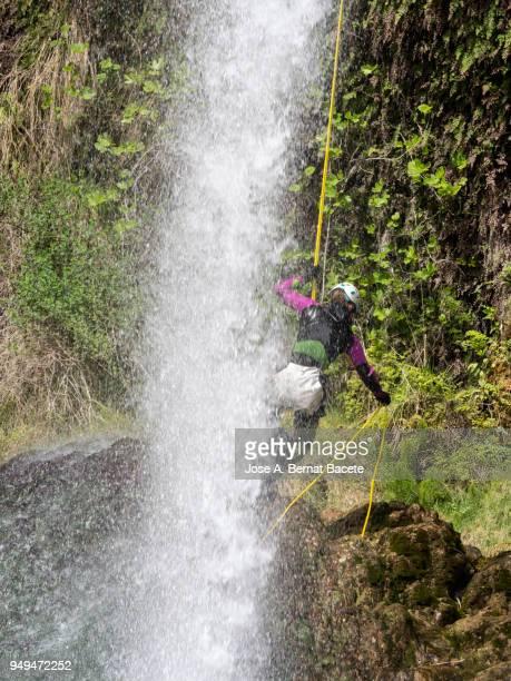 Climbing woman, climbing a rock wall close to a water waterfall.
